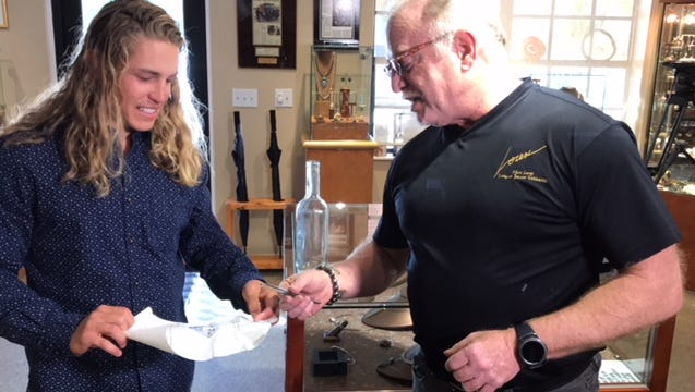 Mark Loren from Mark Loren Designs shows Wes Skinner the $10,000-plus retail diamond he won by finding a specific message in a bottle floating in the Gulf of Mexico, part of a Valentine's Day promotion by the jeweler.