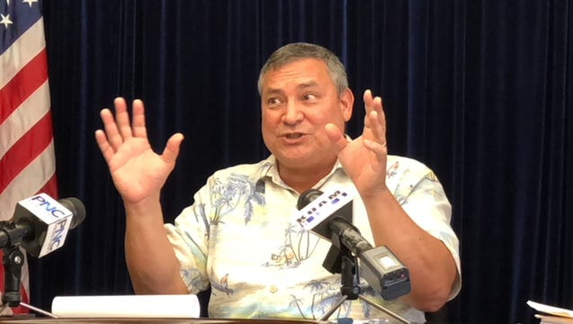 Gov. Eddie B. Calvo gestures shortly before signing on Friday afternoon a bill raising business privilege tax by 25 percent for six months and then a 2 percent sales tax by Oct. 1, with provision requiring cutting government cost by at least $30 million, to help address a $67 million budget shortfall as a result of a federal tax reform law.