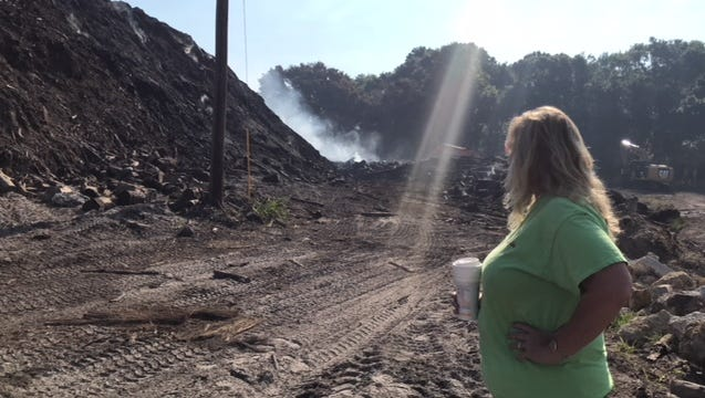 Denise Houghtaling, owner of MW Horticulture Recycling, watches smoke drifting from a fire at the company's property on East Street in North Fort Myers.