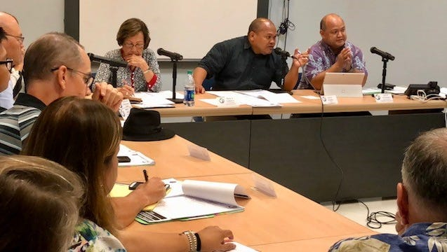 Guam Education Board Chairman Mark Mendiola, second from right, gestures as he addresses the crowd Tuesday night during a regular board meeting at Tiyan. The board adopted a policy allowing high school students to use any school bag of their choice as long as there are no vulgar language or inappropriate images, no hidden pockets, and no keychains or other articles that can be used for violence.