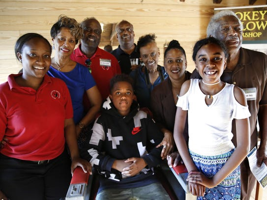 Zadia Ash, front right, great-granddaughter of Civil Rights activist and barber Eddie Barrington, poses with other members of the Barrington family around his barber chair at the grand opening of the Smokey Hollow Barber Shop at the Smokey Hollow Commemoration in Cascades Park Monday.