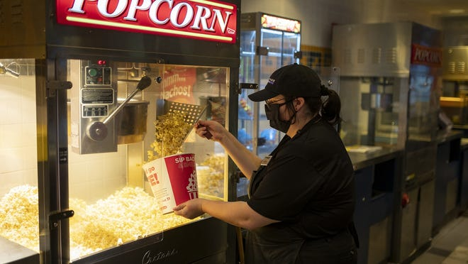 Employee Alex Bonin serves up some fresh popcorn at Blackstone Valley 14 Cinema de Lux in Millbury. It is one of few Central Mass. movie theaters to have reopened amid the COVID-19 pandemic.
