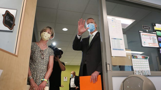 Secretary of Health and Human Services Marylou Sudders and  Gov. Charlie Baker  wave to students through a classroom door as they tour The New England Center for Children on July 13 in Southboro.