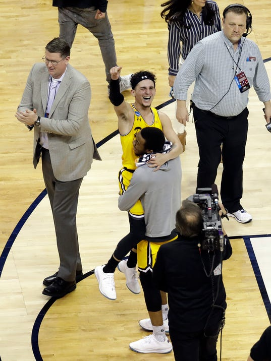 UMBC's K.J. Maura, center, celebrates with a teammate after UMBC defeated Virginia 74-54 in a first-round game in the NCAA men's college basketball tournament in Charlotte, N.C., Friday, March 16, 2018. (AP Photo/Chuck Burton)