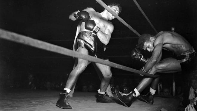 1943: Jake LaMotta, left, knocks Sugar Ray Robinson through the ropes for a count of nine.