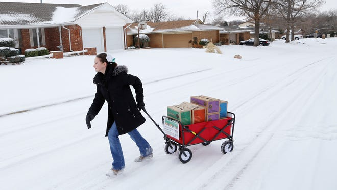 Girl Scout Katie Francis pulls her wagon full of boxes of cookies in the snow selling cookies in Oklahoma City.