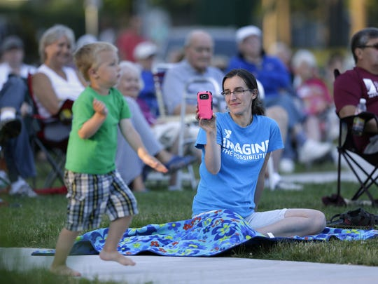 Hannah Schraufnagel records her son, Isaac, 3, while he dances at the Appleton City Band's performance Tuesday at Pierce Park in Appleton.