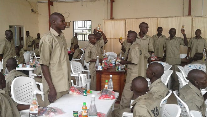 Surrendered Boko Haram Islamic militants receive breakfast before being loaded onto an aircraft by the Nigerian military prior to be taken to a rehabilitation centre in Gombe.