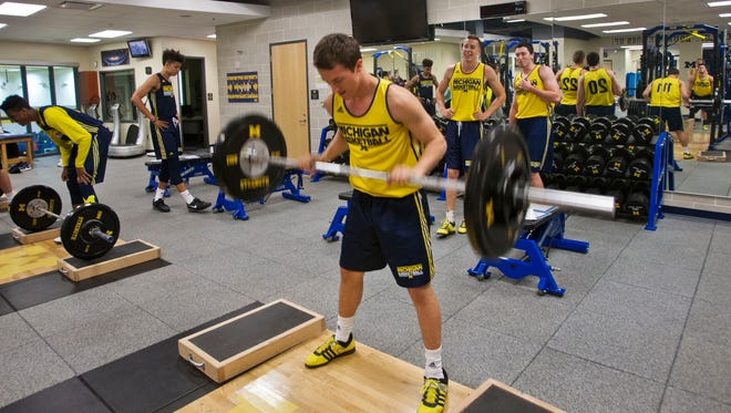 Michigan guard Andrew Dakich does a strength-training exercise at the Crisler Center in Ann Arbor on Oct. 2, 2015.