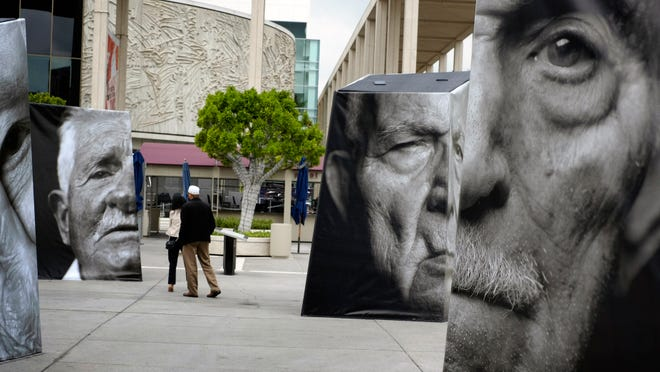Visitors view an outdoor installation called iwitness, a grouping of 20 larger-than-life 3-D photo sculptures of Armenians survivors, at the Music Center Plaza in downtown Los Angeles on Friday, April 24, 2015. The exhibit is part of events memorializing the centenary of the 1915 killings of an estimated 1.5 million Armenians during the Ottoman Empire rule of Turkey, while elsewhere in Los Angeles demonstrators pressed for recognition by Turkey and the U.S. that it was genocide.