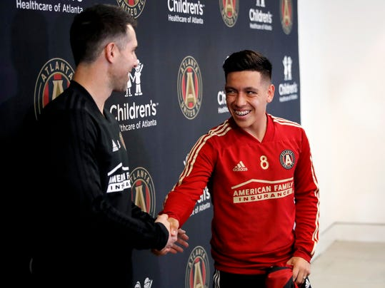 Ezequiel Barco, of Argentina, right, shakes hands with Carlos Bocanegra, Atlanta United vice president and technical director, following a news conference introducing Barco to the MLS soccer team in Marietta, Ga., Thursday, Feb. 15, 2018. Atlanta United has high expectations for a new, young star in its second season after paying an MLS-record transfer fee of $15 million for 18-year-old Barco. Barco joins Atlanta's wave of young stars from South America that also includes Miguel Almiron, Hector Villalba and Josef Martinez. (AP Photo/David Goldman)
