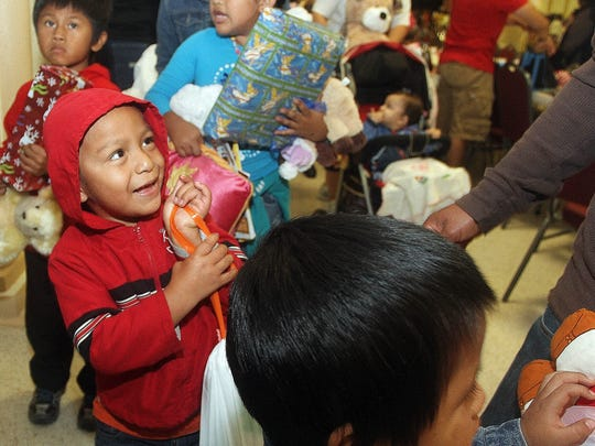 Omar Carrillo,4,  smiles as he hands his gifts over to be placed in a bag at the annual Nations Association Christmas Party Saturday at the Shriner's Temple on Hanson St. in Fort Myers. Hundreds of needy children received gifts that were donated in Southwest Florida.
