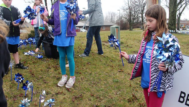 Young volunteers plant pinwheels outside the campus of Marion County Children Services on Marion-Waldo Road.