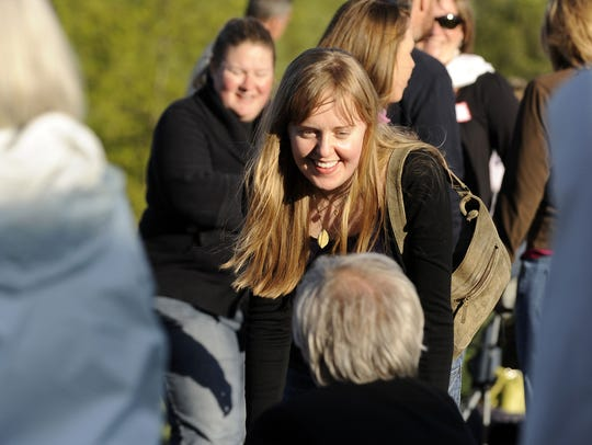 Sarah Pharis smiles as she speaks with others gathered