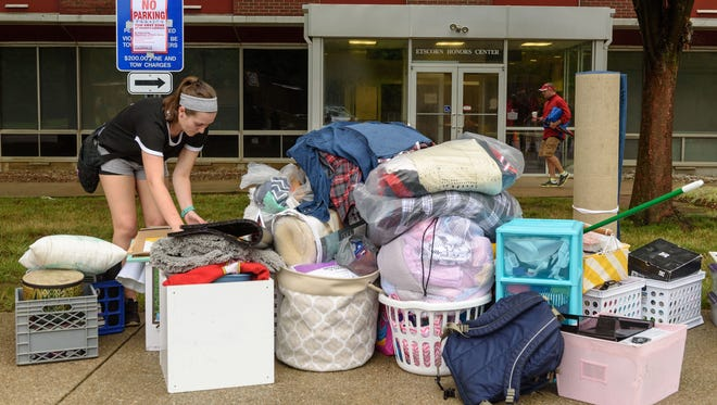 Freshman Mollie Sullivan, 18, piles her stuff on the sidewalk outside Threlkeld Hall as first-time students move in to Belknap Campus dormitories at the University of Louisville in August 2016.