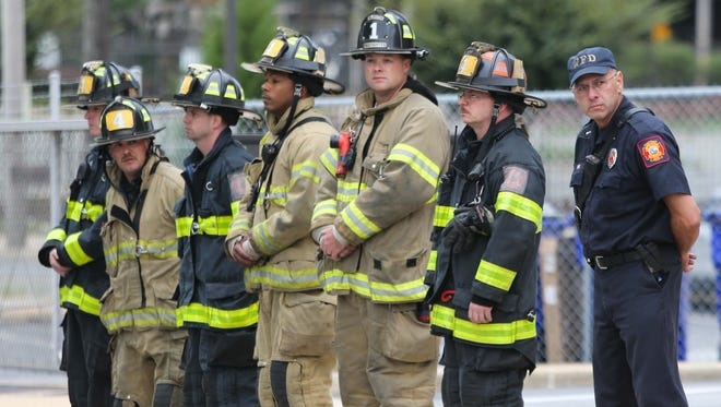 Firefighters line Chestnut Street outside of the medical examiner's office in Wilmington as they await the arrival of a motorcade carrying firefighters who lost their lives fighting a blaze early Saturday morning.