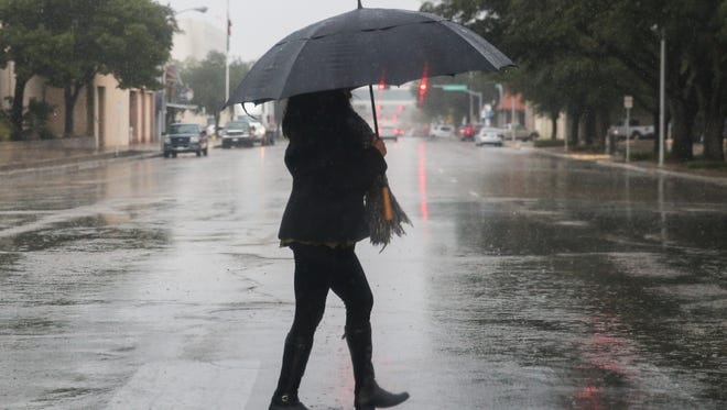 A pedestrian walks across the street during a rainstorm in downtown San Angelo.