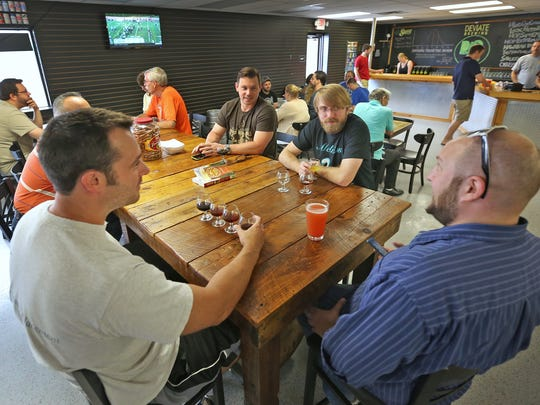 Jeremy Adams, from left counterclockwise, Tom Wilkins, Mike Bodnar, and Jake Springman enjoy a variety of beers at Deviate Brewing, Saturday, August 29, 2015.