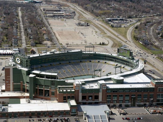 Lambeau Field overlooks the multiple properties, top, purchased by the Green Bay Packers for their Titletown District in this aerial view looking west April 15, 2015.