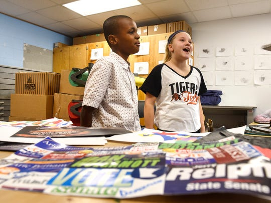 South Junior High School students Natalie Lage and Mohamed Yussuf talk Monday, Nov. 21, about their work with classmates to create collages made of campaign mailers. The works of art that the students created are currently on display at St. Cloud Public Library.