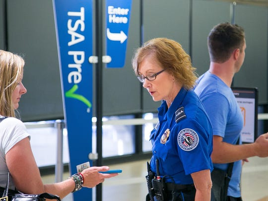 TSA agents direct passengers at the PreCheck security line at Phoenix Sky Harbor International Airport.