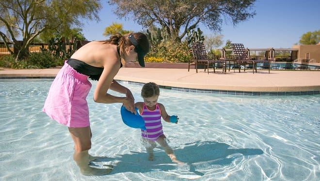 Melissa Barker and her daughter Eden, 2, play at the pool at Desert Camp Community Center in DC Ranch in Scottsdale on Tuesday, April 8, 2014.