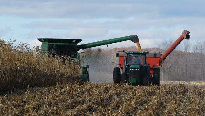 Mike Opificius discharges corn from a combine into a wagon pulled by a tractor operated by John Printz.
