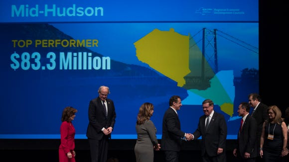 New York Gov. Andrew Cuomo, center, greets representatives of the Mid-Hudson Regional Economic Development Council during an economic development awards ceremony on Thursday, Dec. 8, 2016, in Albany, N.Y. (AP Photo/Mike Groll)
