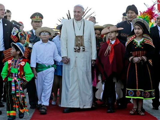 FILE - In this Wednesday, July 8, 2015 file photo, Pope Francis holds hands with children wearing traditional clothing as he walks with Bolivian President Evo Morales, background right, upon his arrival at the El Alto airport in Bolivia.