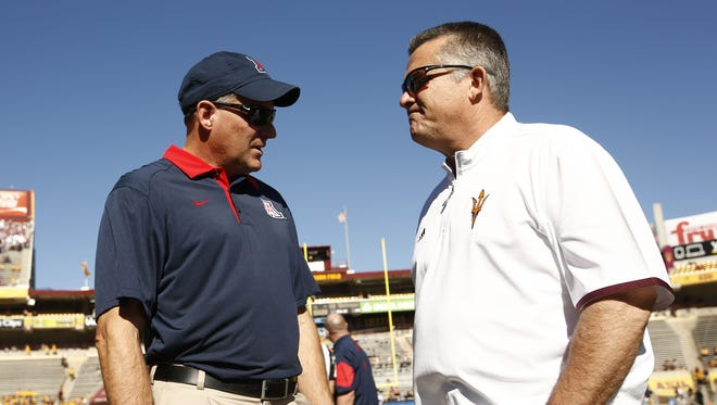 Arizona head coach Rich Rodriguez visits with Arizona State head coach Todd Graham before the 89th Territorial Cup on Nov. 21, 2015 in Tempe, Ariz.
