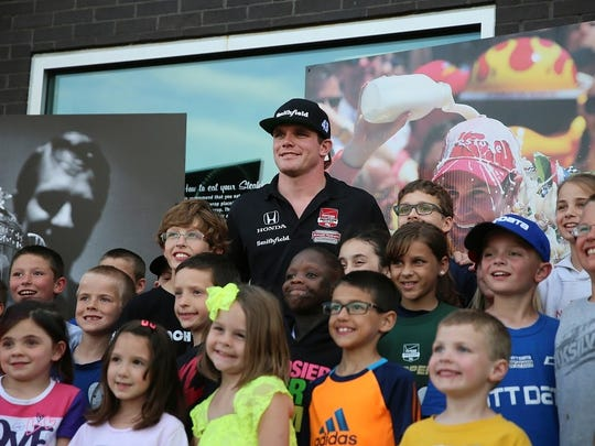 IndyCar driver Conor Daly poses with children from the audience at Curt Cavin's Carb Night Burger Bash in 2015. This year's event is scheduled for May 27 on Pan Am Plaza.