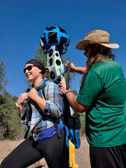Andy Fuzak helps Katherine Beal shoulder the 46-pound Google Trekker camera system to record a trail in Riverside State Park for the public to view online.