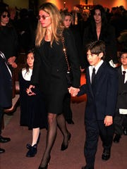 -  -Mary Bono, widow of Rep. Sonny Bono, leads her daughter, Chianna, and son, Chesare, out of St. Theresa Catholic Church in Palm Springs following services for Bono on Friday, Jan. 9, 1998