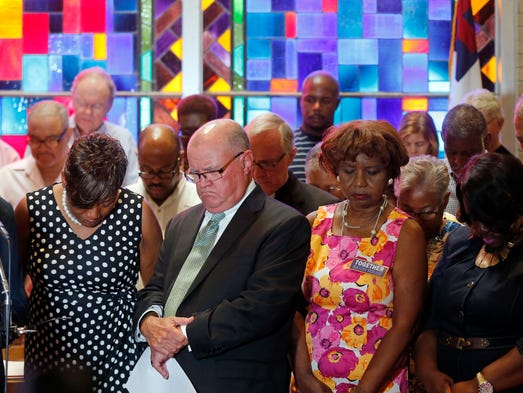 Members of Together Baton Rouge bow their heads in