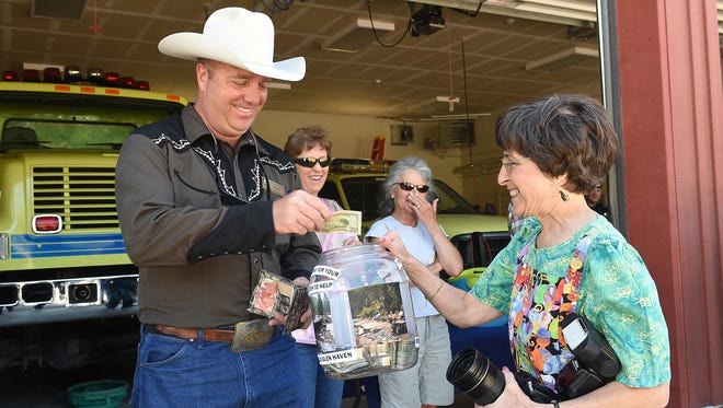 Longtime Glen Haven resident Marsha Hobert, right, solicits a donation for the town from Cody Rex Walker, a trustee of the Town of Estes Park, in Glen Haven in this file photo. The community is now raising money to rebuild its town hall.