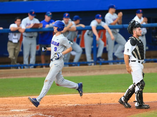 Florida's Christian Hicks (9) scores a run past Wake Forest catcher Ben Breazeale in the fifth inning of an NCAA college super regional baseball game Sunday, June 11, 2017, in Gainesville, Fla. (AP Photo/Matt Stamey)