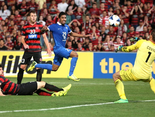 Saudi Arabia's Al Hilal's Salem Al-Dossari heads the ball for a goal attempt as Western Sydney Wanderers' goalkeeper Ante Covic defends it during their Asian Champions League Final soccer match in Sydney, Australia, Saturday, Oct. 25, 2014. The Wonderers won the match 1-0. (AP Photo/Rob Griffith)