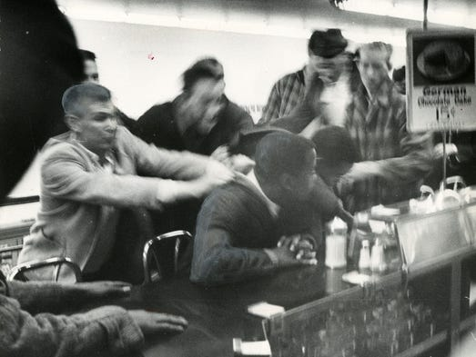 John Lewis is pulled off a stool during a sit-in at