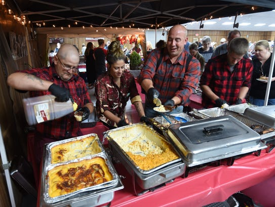 Workers at the Holy Smokes BBQ booth scramble to plate items during Tuesday night's Taste of the Twin Lakes fundraiser. The Mountain Home barbecue restaurant picked up the People's Choice award in the casual dining category.