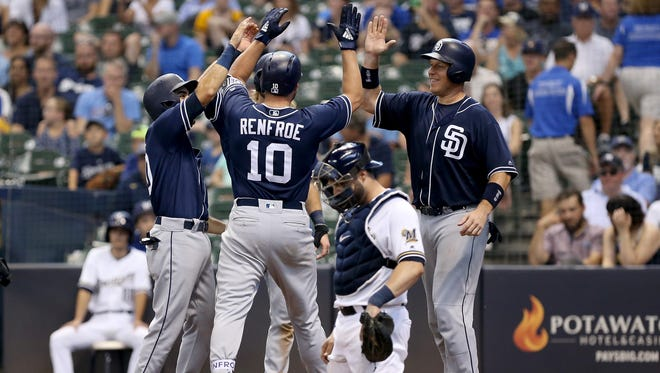 Hunter Renfroe is greeted by some elated teammates after crossing the plate much to the dismay of Brewers catcher Manny Pina after Renfroe's grand slam in the ninth inning gave the Padres the lead.