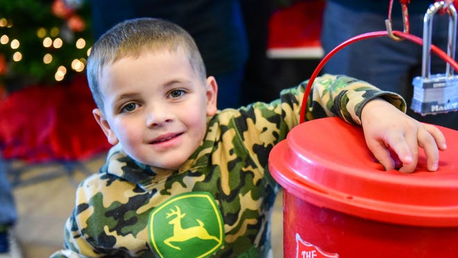 Brayden Rowe donates to the Salvation Army on Dec. 19, 2015.