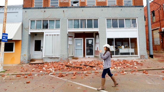 """A television reporter takes video as she walks past a damaged building in Cushing, Okla. caused by Sunday night's 5.0 magnitude earthquake, Monday, Nov. 7, 2016. Dozens of buildings sustained """"substantial damage"""" after a 5.0 magnitude earthquake struck Cushing, home to one of the world's key oil hubs, but officials said Monday that no damage has been reported at the oil terminal. (Jim Beckel The Oklahoman via AP) ORG XMIT: OKOKL201"""
