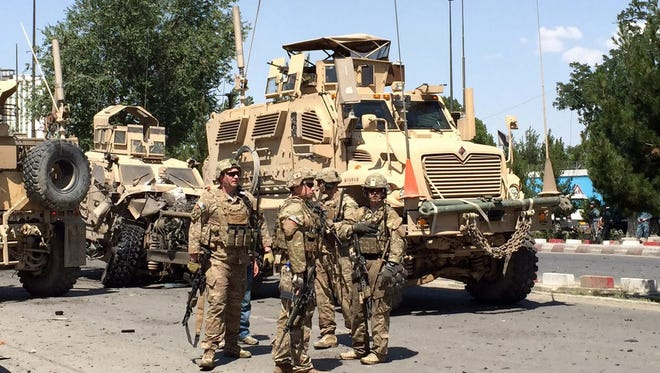 NATO soldiers stand guard near the site of a suicide bomb blast that targeted a convoy of foreign troops in Kabul, Afghanistan, June 30, 2015.