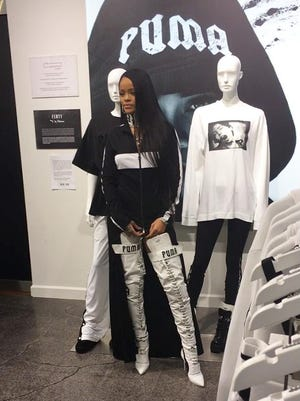 Rihanna poses next to items from her new fashion collection for Puma at Foot Locker in New York.