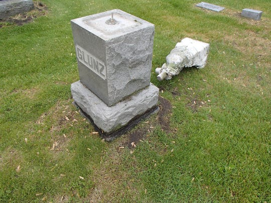 A damaged headstone sits at Immaculate Conception Parish cemetery on Church Road in Ira Township.