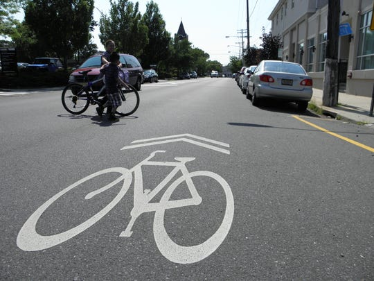 """A woman and her daughter walk a bike across Chestnut Street in Red Bank which is marked with """"sharrows"""" reminding drivers to share the road with bicycles. Marking Monmouth County roads with sharrows and painting bike lanes where they are wider has been proposed by Fair Haven Mayor Benjamin Luccarelli."""