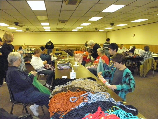Volunteers at the 2011 Sew-A-Thon in Algonac place cords in the draw string care bags given to area foster children.