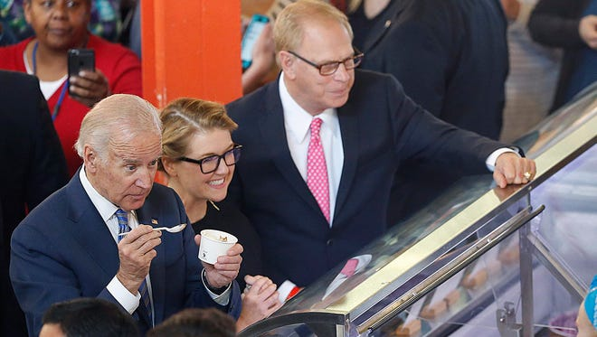 Vice President Joe Biden and Jeni's Spendid Ice Cream's founder Jeni Britton Bauer order some ice cream from her shop in the North Market Wednesday, May 18, 2016 in Columbus, Ohio. More than 4 million U.S. workers will become newly eligible for overtime pay under rules issued Wednesday by the Obama administration. The rule seeks to bolster overtime protections that have been eroded in recent decades by inflation. (Chris Russell/The Columbus Dispatch via AP) MANDATORY CREDIT ORG XMIT: OHCOL101