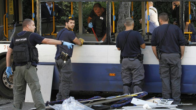 Israeli police officers inspect a bus after an explosive device detonated in a Tel Aviv suburb on Dec. 22.