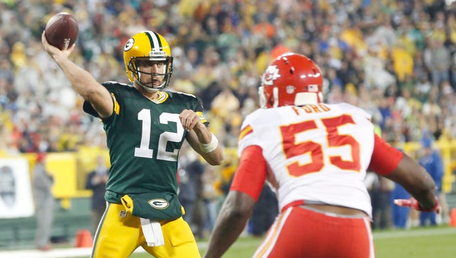 Green Bay Packers' Aaron Rodgers throws with Kansas City Chiefs' Dee Ford rushing during the second half Monday. Rodgers threw five TDs in the Packers' 38-28 victory.